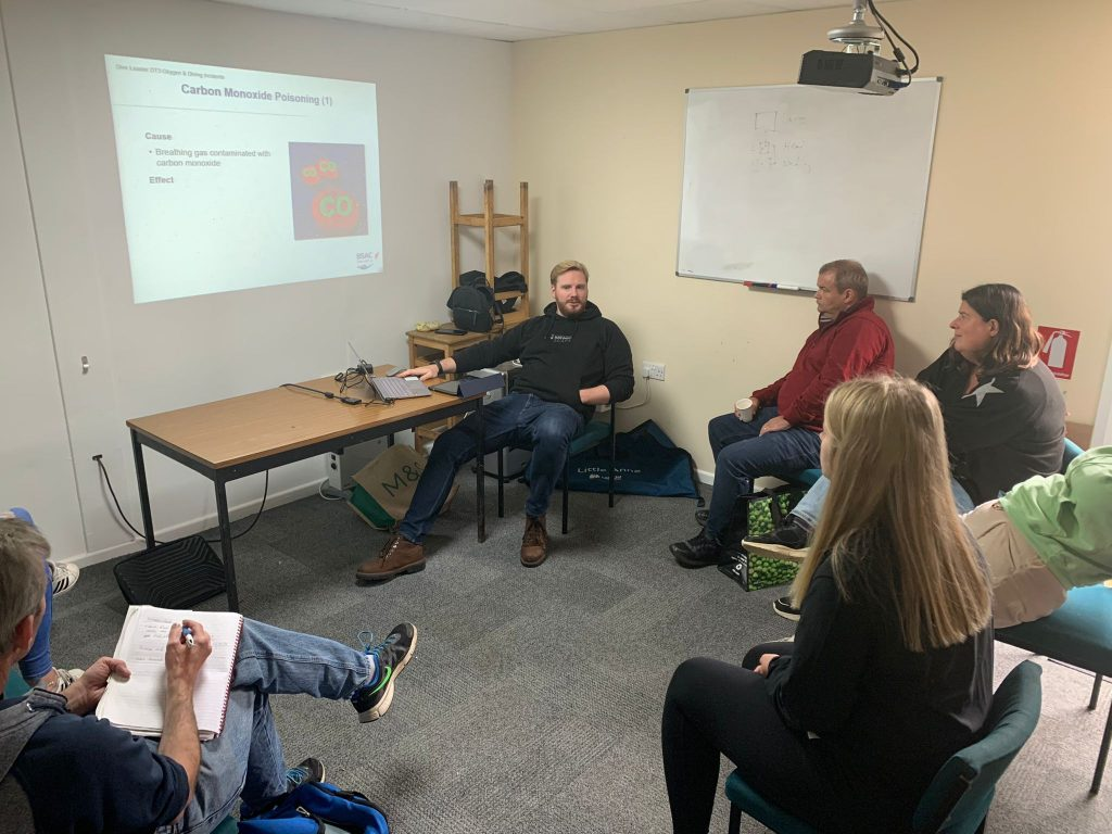 Oxygen Administration Training - image of students sitting listening to instructor presenting course material on projected screen.