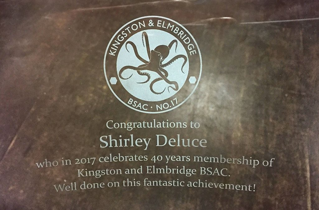 "A picture of Inscription written on the glass trophy. Inscription Reads ""Congratulations to Shirley Deluce who in 2017 celebrtes 40 years membership of Kingston and Elmbridge BSAC. Well done on this fantastic achievement."""