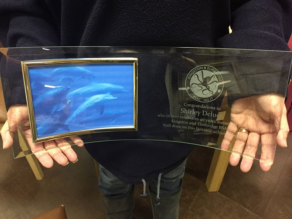 "A close up picture of Shirley's Glass Trophy that has a picture of dolphins on one side and an inscription on the other. Inscription Reads ""Congratulations to Shirley Deluce who in 2017 celebrtes 40 years membership of Kingston and Elmbridge BSAC. Well done on this fantastic achievement."""